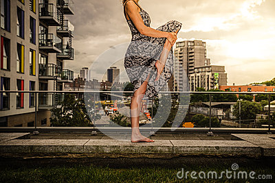 Young woman raising her leg on roof top