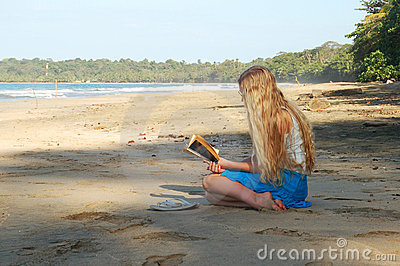 Young woman reading on beach