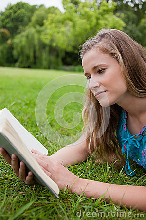 Young woman reading a book while lying down