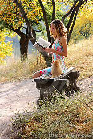 Young woman reading a book. Near it is the cat