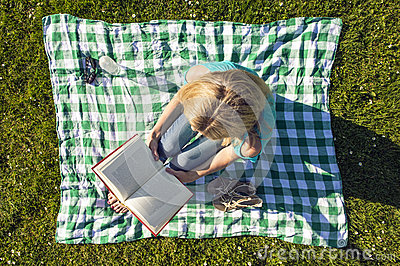 Young Woman Reading Book In Park, seen from above