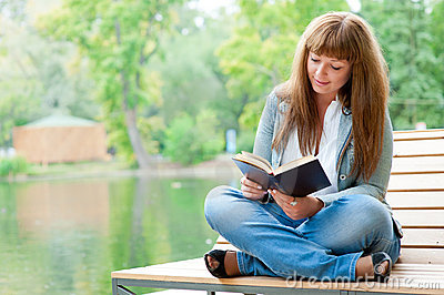 Young woman reading a book sitting on the bench