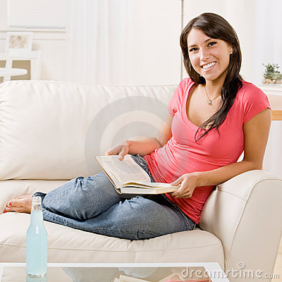 Young woman reading book on sofa at home