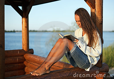 Young woman reading book on sunset