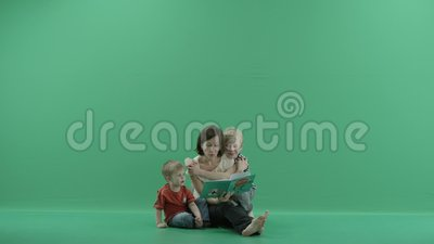 Young woman is reading a book to the children. Young woman is reading a book to the 3 years old boy and 10 years old boy run and hugs her on green screen stock video