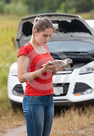 Free Young Woman Reading Manual Book For Her Broken Car Royalty Free Stock Photo - 116682645