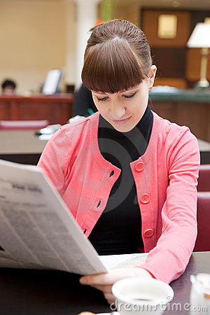 Young woman reading newspaper in hotel lobby