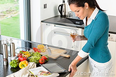 Young woman reading tablet recipe kitchen cooking