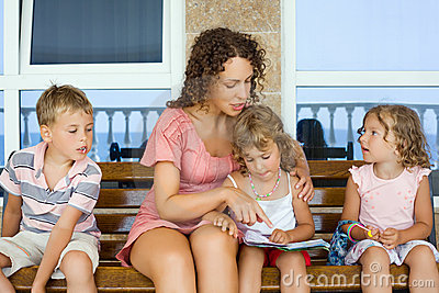 Young woman reads book to two little girls and boy