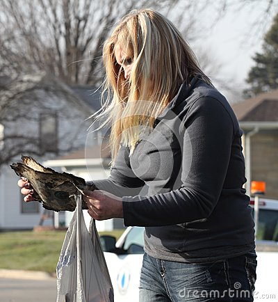 Young woman reads charred document after fire