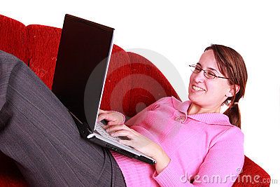 Young woman on red couch using notebook