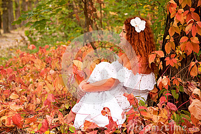 Young woman among red leaves
