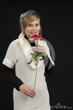 Young woman with red rose on black