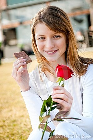 Young woman with red rose and chocolate