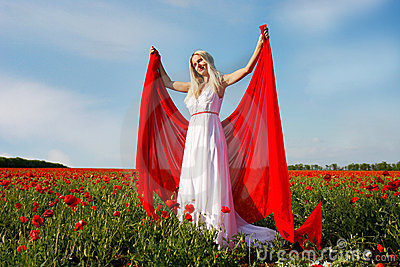 Young woman with red scarf in poppy field