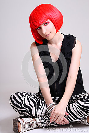 Young woman in red wig sitting