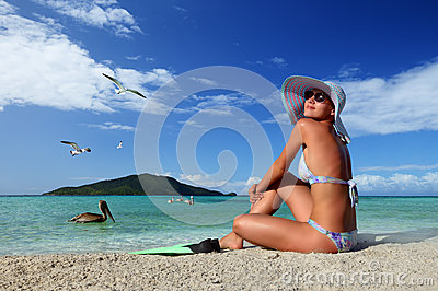Young woman relaxing on the beach enjoying the flying birds against the green islands
