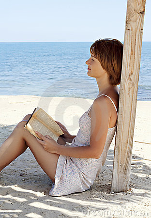 Young woman relaxing with a book near the sea