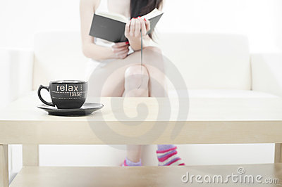 Young woman relaxing in a sofa and reading a book
