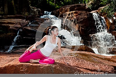 Young woman relaxing by the waterfall