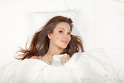 Young woman relaxing in white bedding