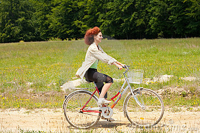 Young woman riding a bike on country road