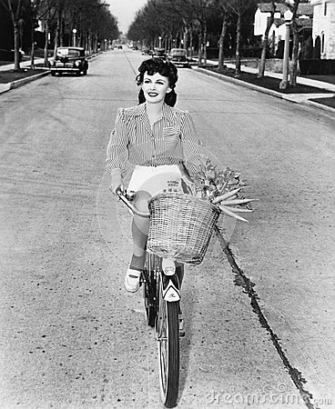 Free Young Woman Riding Her Bicycle With Basket Full Of Flowers And Carrots Royalty Free Stock Photo - 52012635