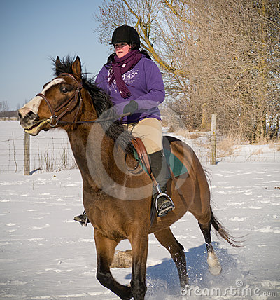 Young Woman riding horse in winter
