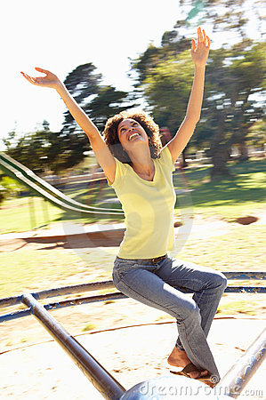Young Woman Riding On Roundabout In Park