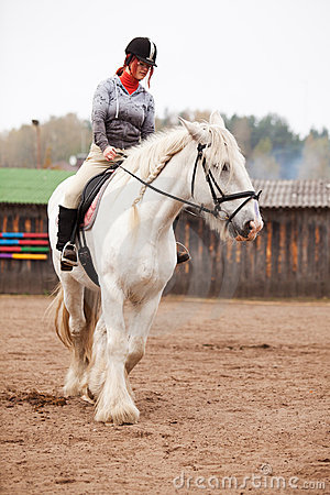 Young woman riding shire horse