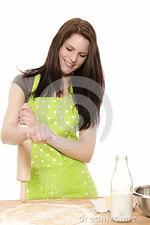 Young woman with rolling pin adding flour to dough