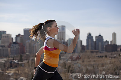 Young woman running in city.