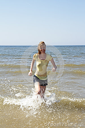 Young woman running out of the water