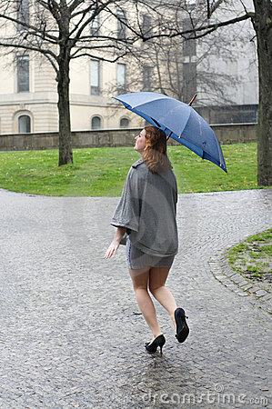 Young woman running through the rain