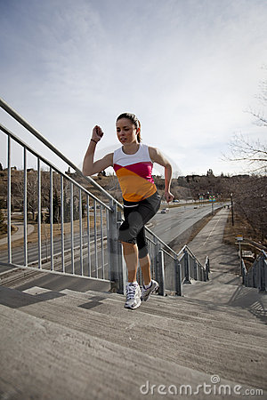Young woman running up stairs in city.