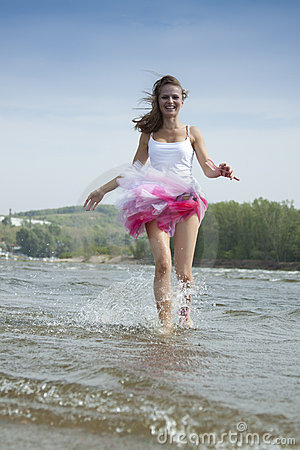 Young woman running through the water at the beach