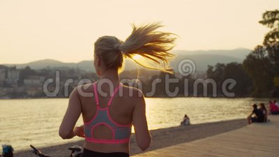 Young woman runs in the morning, the sun is rising brightly, people are sitting by the shore. Slow motion. Young woman runs in the morning, the sun is rising stock video