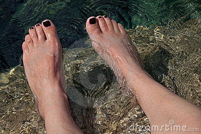 Young woman s manicured feet in water