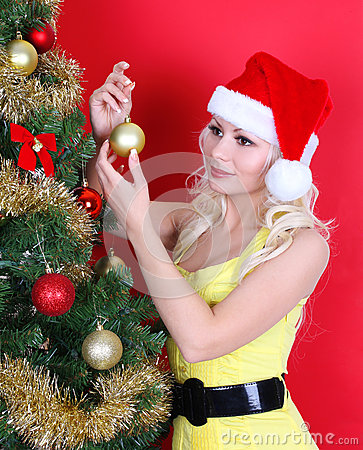 Young woman in Santa hat decorating Christmas tree over red
