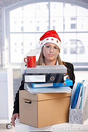 Young woman in santa hat dejected in office