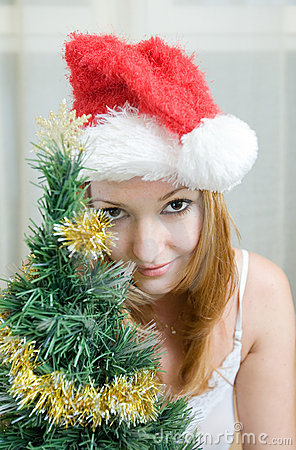 Young woman  in Santa hat near Christmas tree