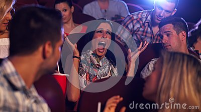 Young woman screaming at cinema