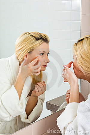 Young Woman searching for wrinkles on her face