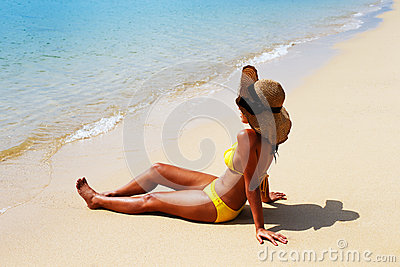 Young woman seating down on a sandy beach and sun bathing