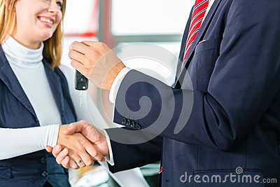 Young woman and seller with auto in car dealership