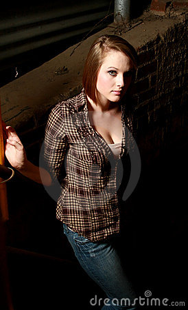 Young woman in a shadowy alley