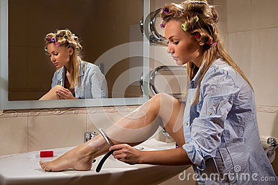 Young woman shaving her leg