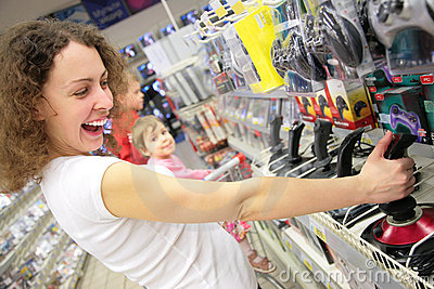 Young woman in shop plays with joystick Stock Photo