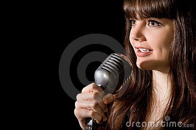 Young woman sing in microphone isolated on black