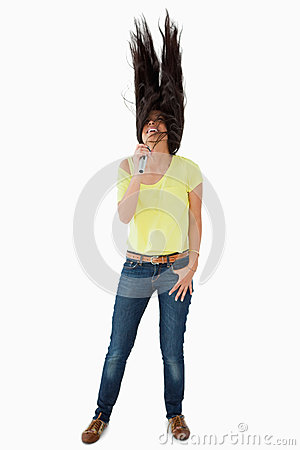 Young woman singing while shaking her head